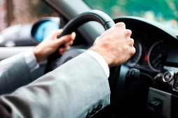 image of driver with hands on the steering wheel